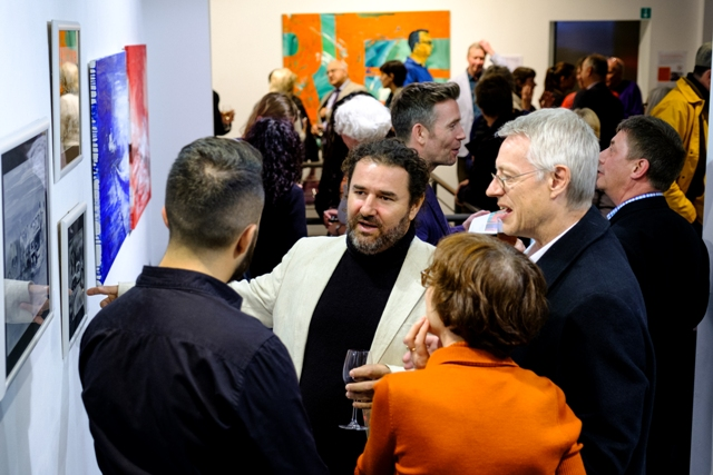 Cuban artist Luis Camejo talks about his work with guests at the opening night