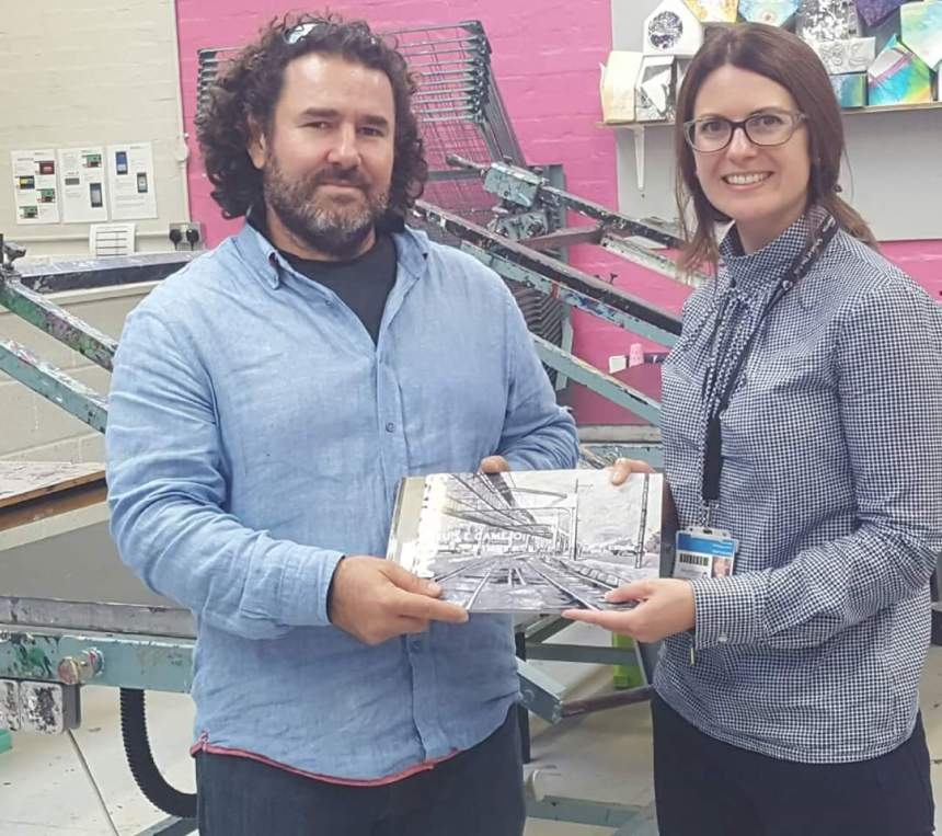 Artist Luis Camejo presents tutor Catriona Leahy with a book of his work at Northampton university